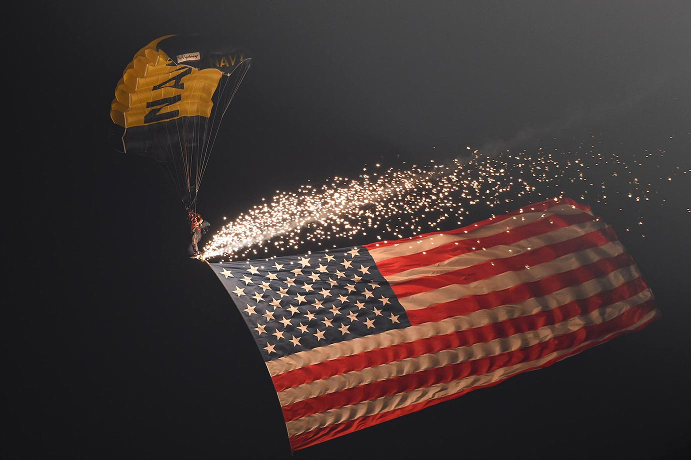A member of the United States Navy parachutes into the Los Angeles Memorial Coliseum.