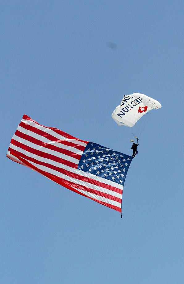 A parachutist delivers the American flag before the Sprint Cup Series 5-Hour Energy 301 400 race at New Hampshire.