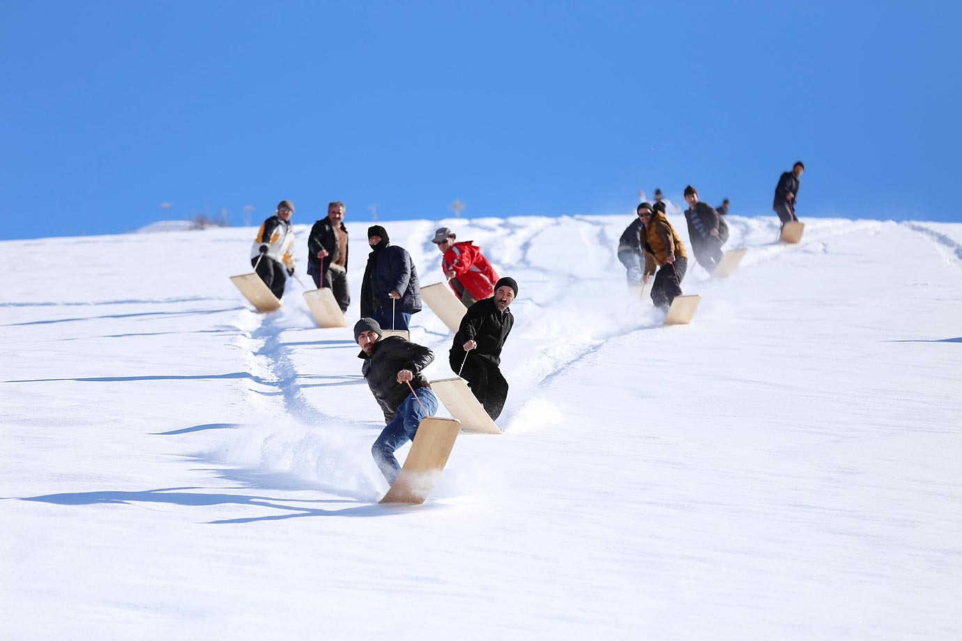 "People ski with a rope attached to a wooden plate named ""Petranboard,"" similar to the first versions of a snowboard, during the 8th Petranboard Skiing Festival in Petran Plateau, Turkey."