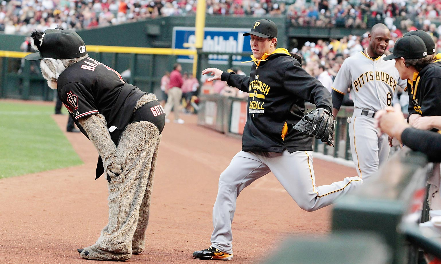 A Pittsburgh Pirates player jokingly pretends to kick Arizona Diamondbacks mascot Baxter before the start of a game.