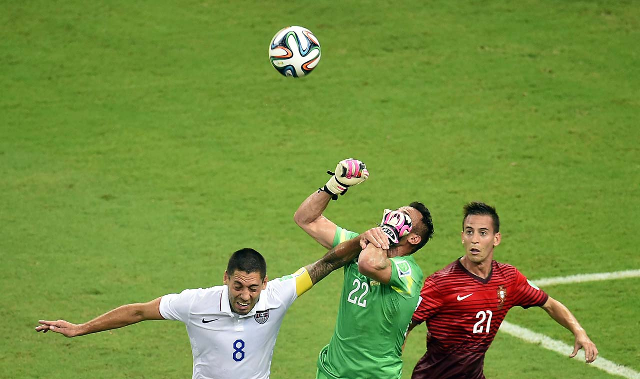Clint Dempsey battles Portugal goaltender Beto.