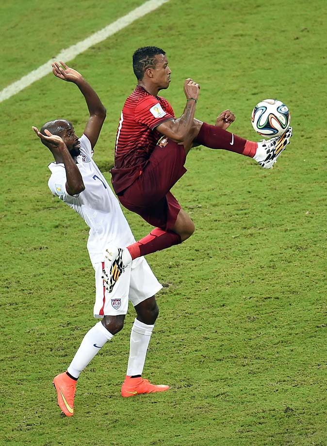 Portugal's forward Nani jumps for the ball in front of DaMarcus Beasley.