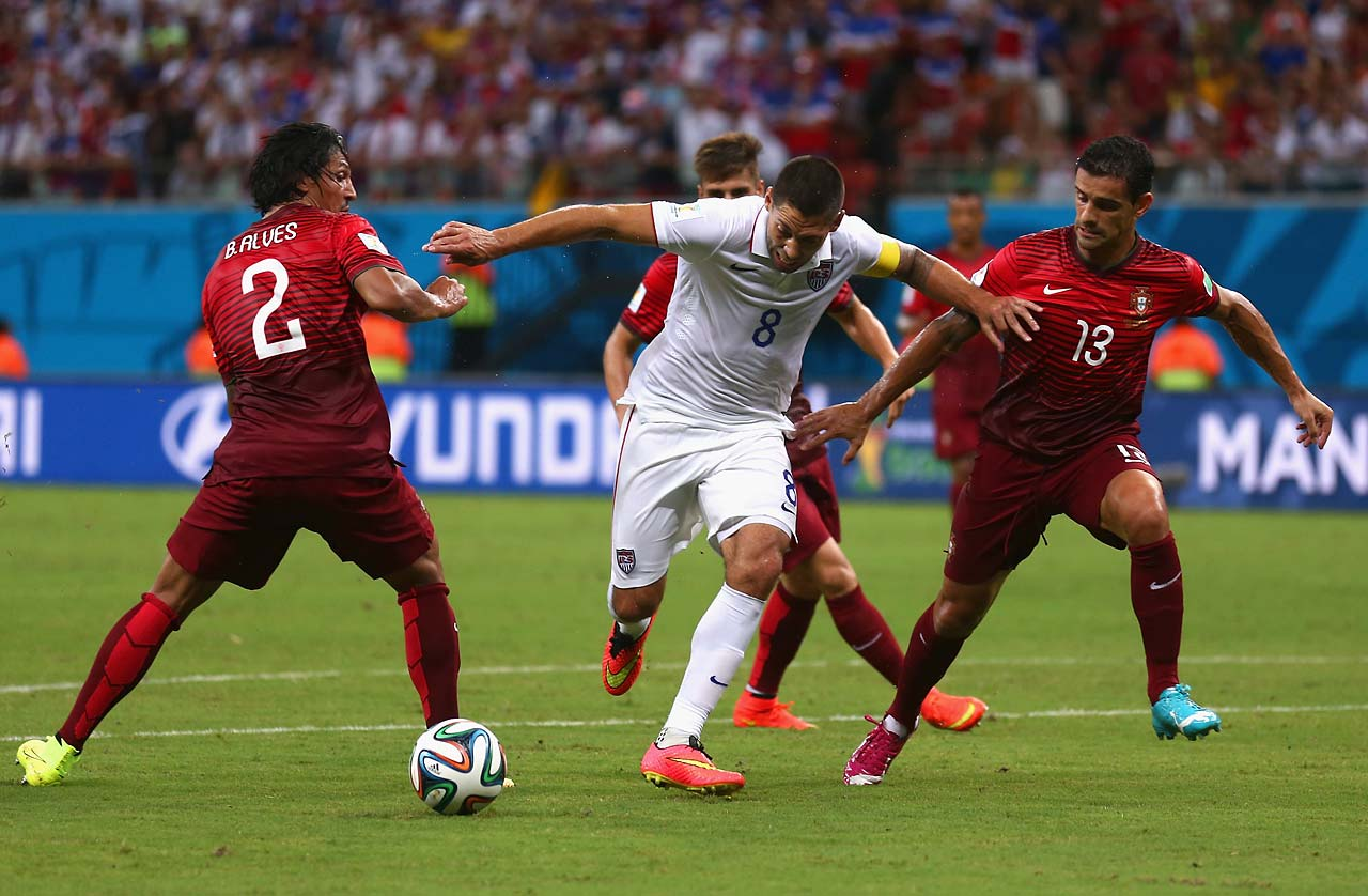 Clint Dempsey is challenged by Bruno Alves and Ricardo Costa of Portugal.