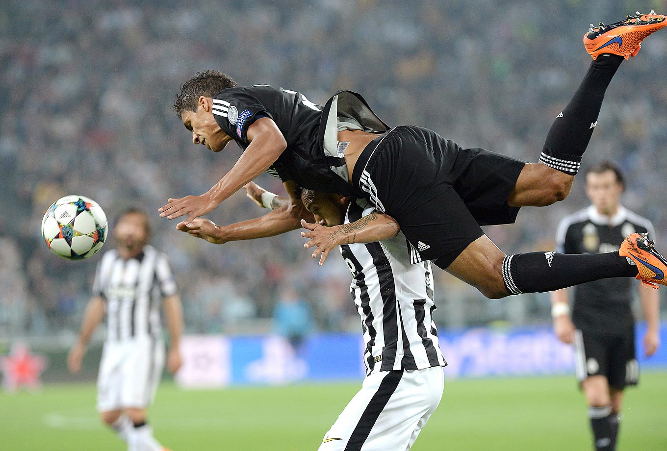 Raphael Varene of Real Madrid jumps over Arturo Vidal of Juventus during a Champions League semifinal soccer match.