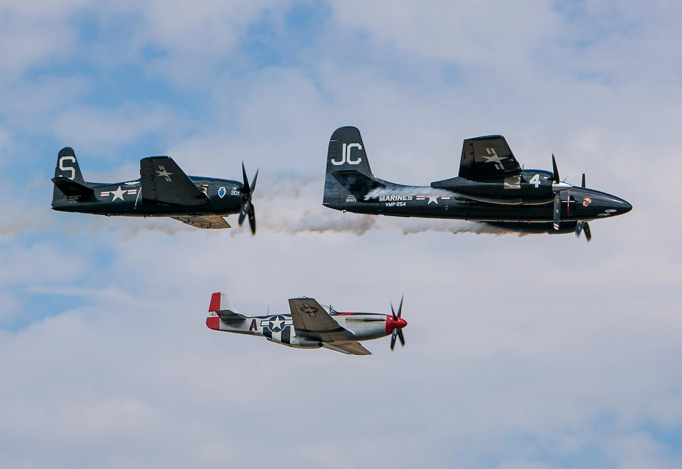 Vintage World War II planes, including a P-51 Mustang fighter (C) and P-38 Lightning (R) and Hellcat bombers fly past the grandstands during the 2013 event.