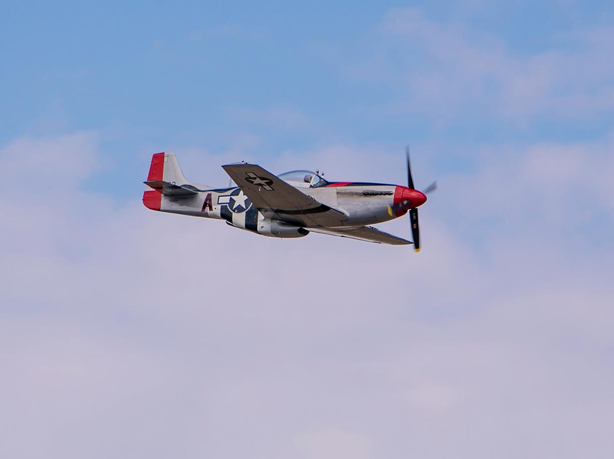 A vintage World War II P-51 Mustang fighter plane flies past the grandstands.