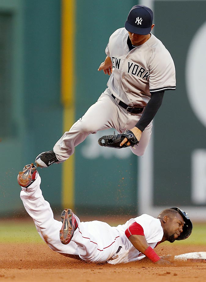 Rob Refsnyder of the New York Yankees jumps over Alejandro De Aza of the Boston Red Sox, who stole second base during the third inning.