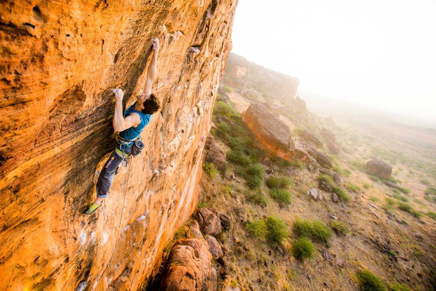 Kilian Fischhuber climbing up the side of a boulder in Badami, India.