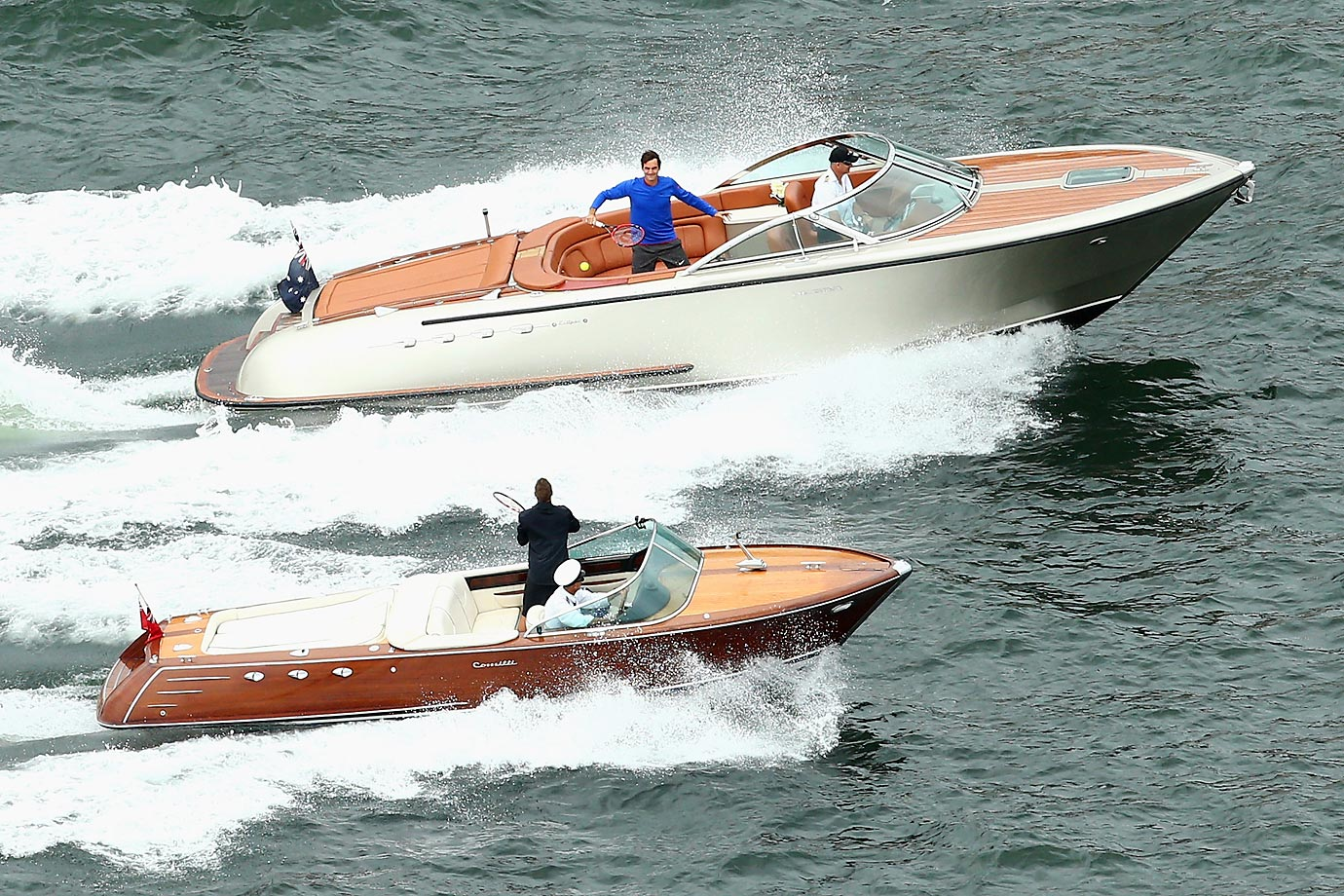 Roger Federer pretends to play tennis with Lleyton Hewitt between speedboats on Sydney Harbour ahead of their Fast 4 Exhibition match on Jan. 12.