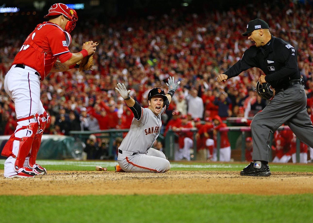 San Francisco's Buster Posey signals to the umpire he's safe after sliding into home in the ninth inning of Game 2 of the NLDS at Nationals Park. The umpires ruled, after review, that catcher Wilson Ramos made the tag in time.