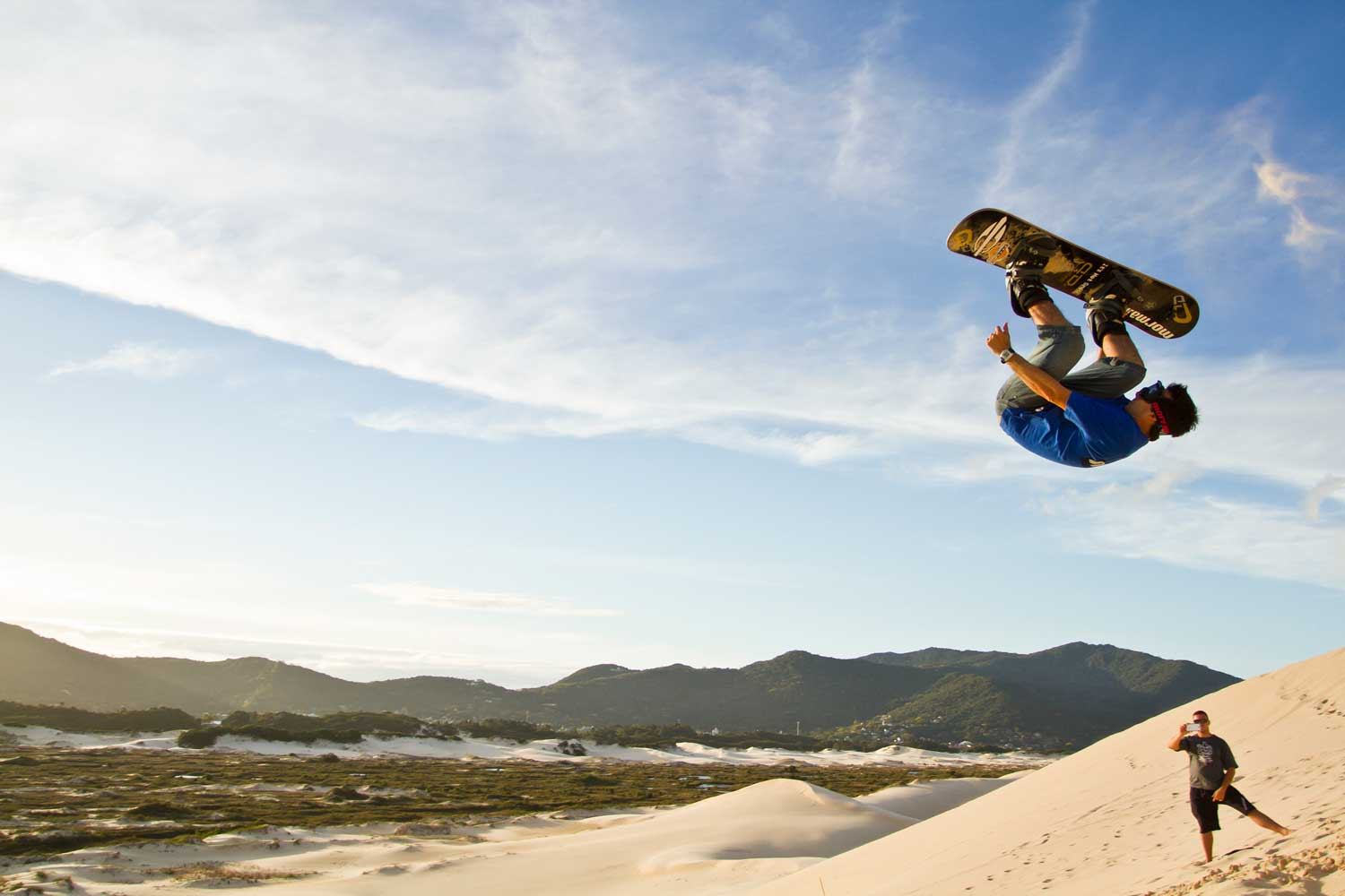 Sandboarding down the dunes of Joaquina Beach in Florianópolis, Brazil.