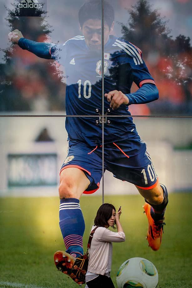 A woman walks past a shop window displaying a poster of Japanese football player Shinji Kagawa on June 11, 2014 in Tokyo.