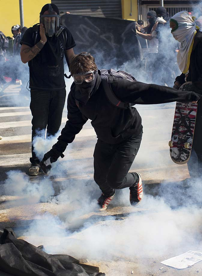 A masked protester returns a tear gas canister to riot police during a June 12 demonstration by people demanding better public services and against the money spent on the World Cup soccer tournament. Brazilian police clashed with anti-World Cup protesters trying to block part of the main highway leading to the stadium that hosts the opening match of the tournament.