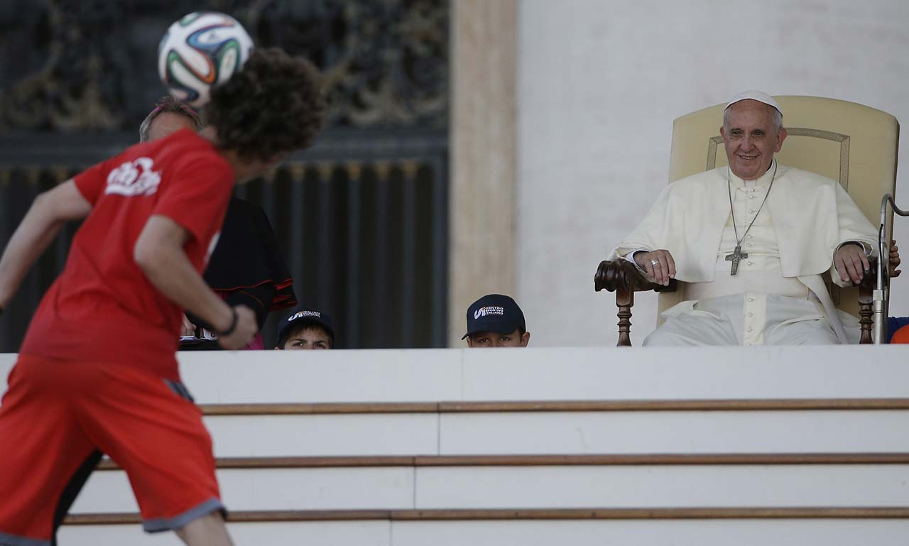 In this photo taken June 7, a soccer player performs in front of Pope Francis during an audience granted to the members of the Italian Sport Centers in St. Peter's Square, at the Vatican. Pope Francis has a message for the World Cup: Let football be a showcase for teamwork and solidarity, not an exhibition of racism and greed. The Argentine-born, football-loving pope recorded a video message that will be broadcast on Brazilian television ahead of the Thursday, June 12, opening match between Brazil and Croatia.