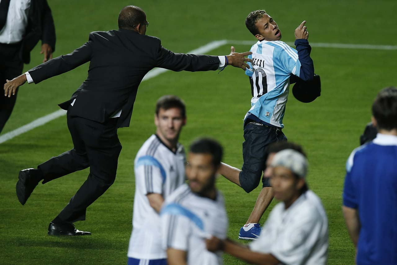 A security guard fails to stop a fan who invaded the pitch wearing an Argentine jersey, top, as Argentina's Lionel Messi, center, and other players look on at the end of a training session at Independencia Stadium in Belo Horizonte, Brazil, on  June 11.