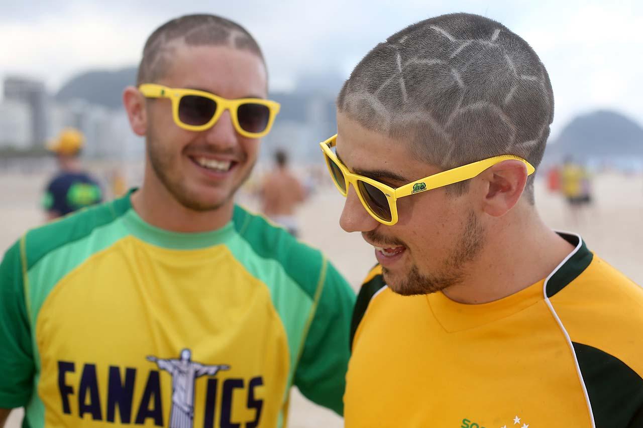 Two Australian football fans show off their football style haircuts at Copacabana beach on June 11.