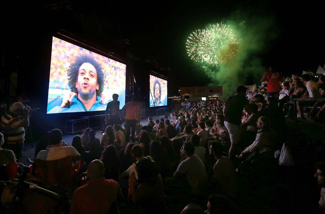 Fireworks are displayed over Lebanese soccer fans who have gathered to watch the first soccer match of the World Cup between Brazil and Croatia, at a fan park, in downtown Beirut, Lebanon, Thursday June 12, 2014.