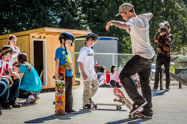 Ryan Sheckler teaches tribal youth how to ollie a skateboard at the Sheckler Foundation's Dedication of the S'klallam Tribe Skate Park.