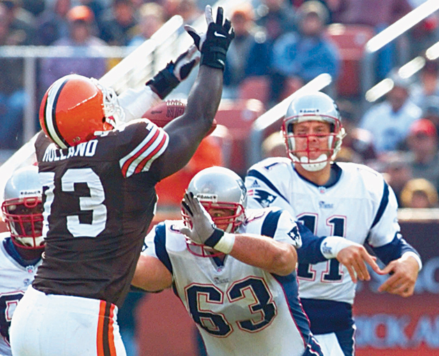 New England Patriots guard Joe Andruzzi (No. 63) in action, blocking for QB Drew Bledsoe. Andruzzi feels guilty that he makes a far bigger salary than his brothers do.