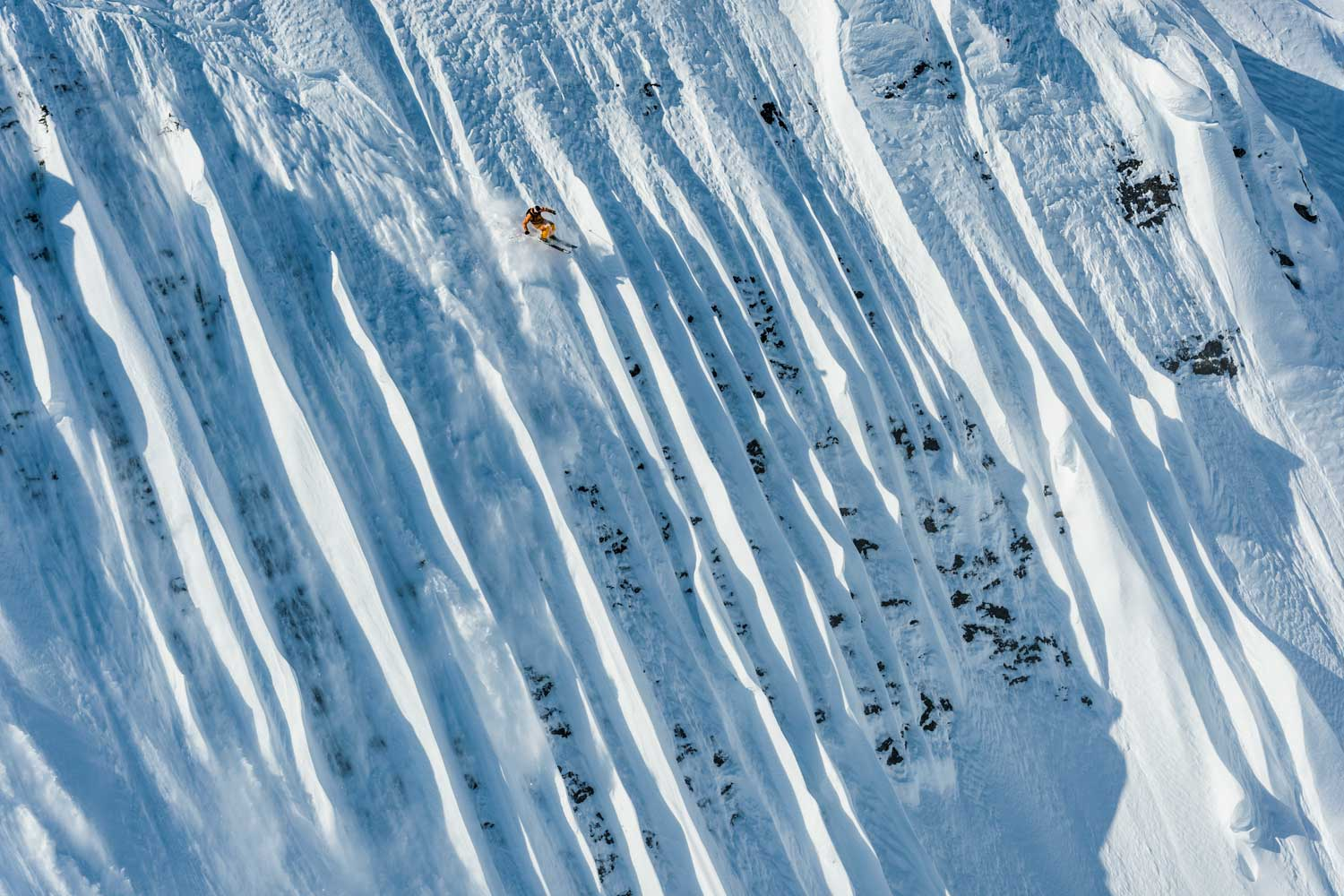 Professional skiers slicing through the side of a snow-covered mountain.