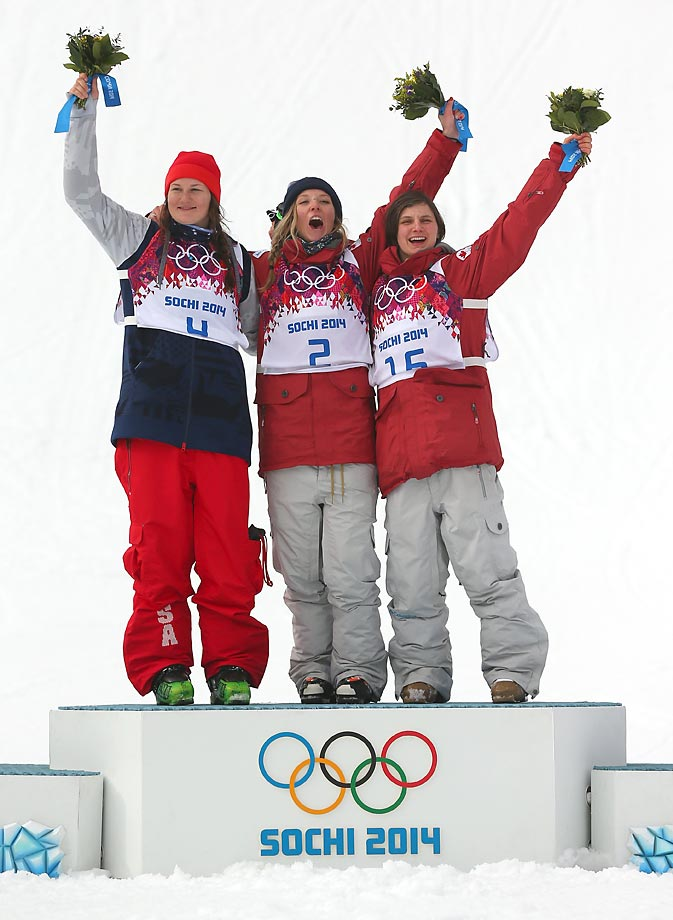 Silver medalist Devin Logan of the United States, gold medalist Dara Howell of Canada and bronze Kim Lamarre of Canada celebrate on the podium during the flower ceremony for the Freestyle Skiing Women's Ski Slopestyle Finals.