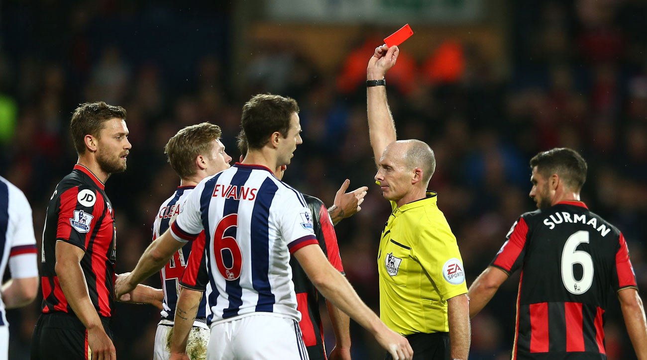 Referee Mike Dean shows the red card in an English Premier League match.