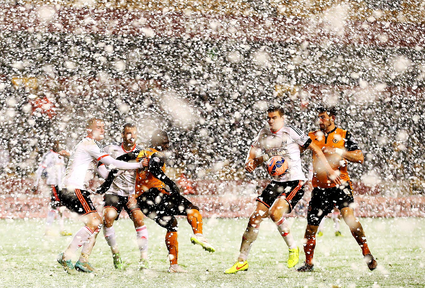 Players battle for the ball as snow falls during the FA Cup third-round replay match between Wolverhampton Wanderers and Fulham at Molineux.