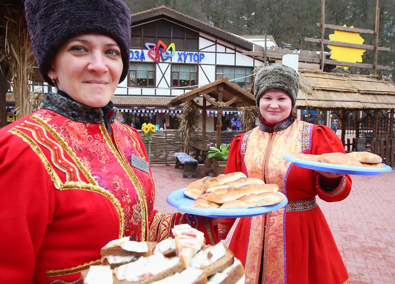 Women dressed in their traditional Russian outfit serve local food at the center of the Rosa Khutor Mountain Cluster village.