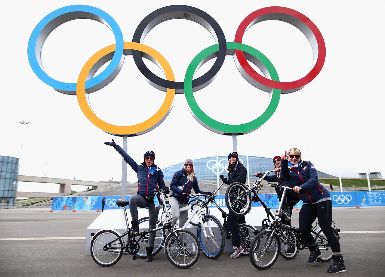 Short track speed skater Alyson Dudek, short track speed skater Emily Scott, speed skater Lauren Cholewinski, speed skater Brittany Bowe and speed skater Sugar Todd of the United States pose with bikes in front of the Olympic rings.