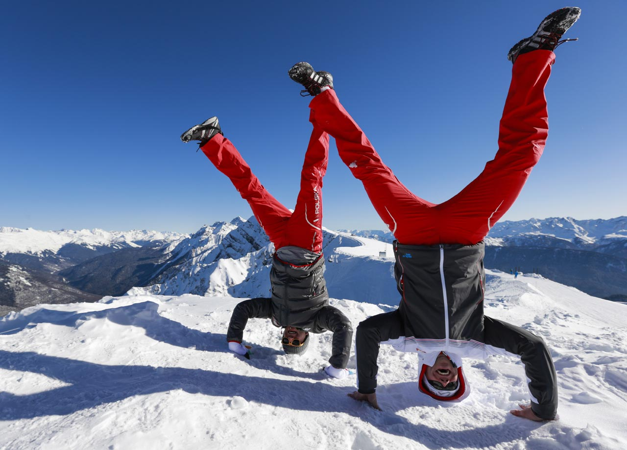 Bobsledder Pawel Mroz, right, and luger Karol Mikrut, both of Poland, do a handstand for a photograph on Rosa Peak, 2320 meters above sea level, at Rosa Khutor ski resort.