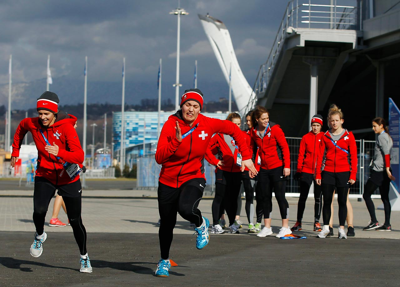 Members of Switzerland's women's ice hockey team warm up at Olympic Park ahead of their practice session.