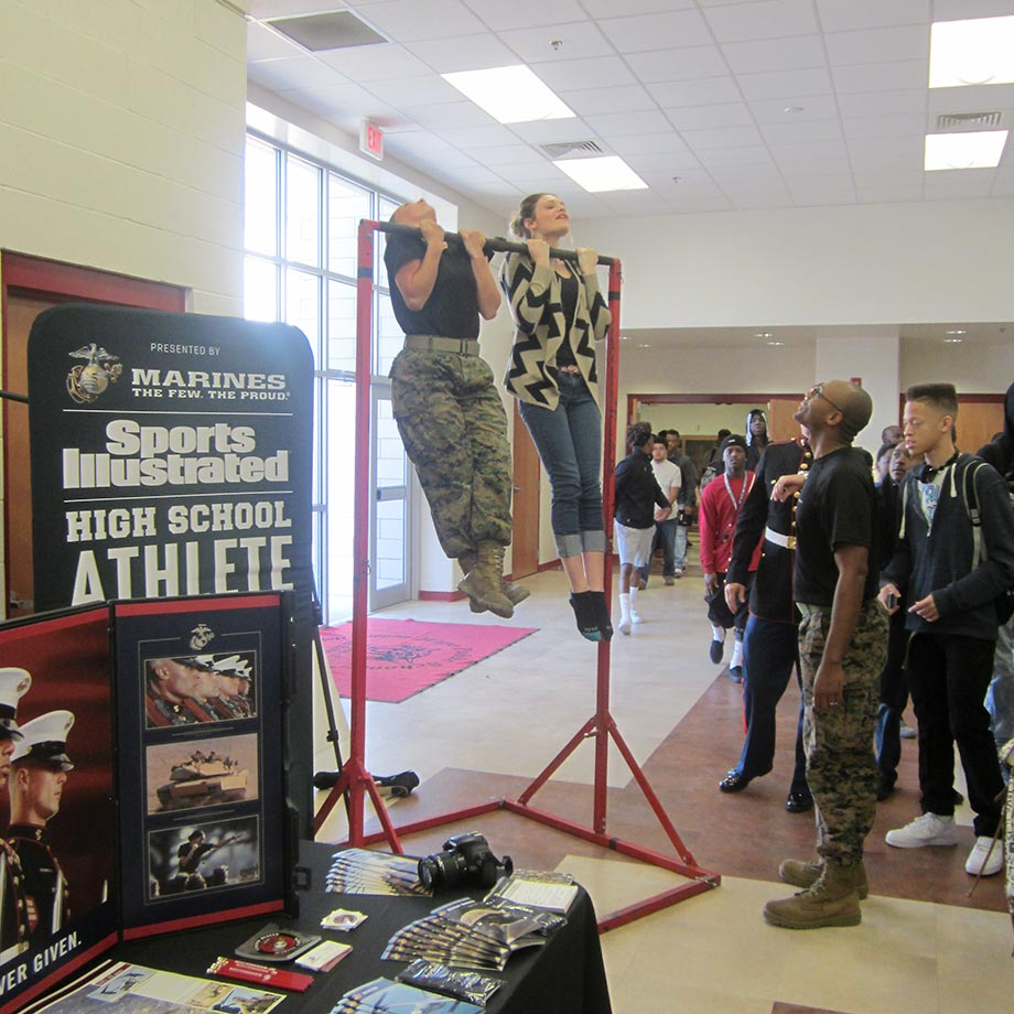 Pvt  Zabrina King helps a Hope High student get the hang of things at the pull-up bar challenge at an event to honor Sosa Agim, the SI High School Athlete of the Month.
