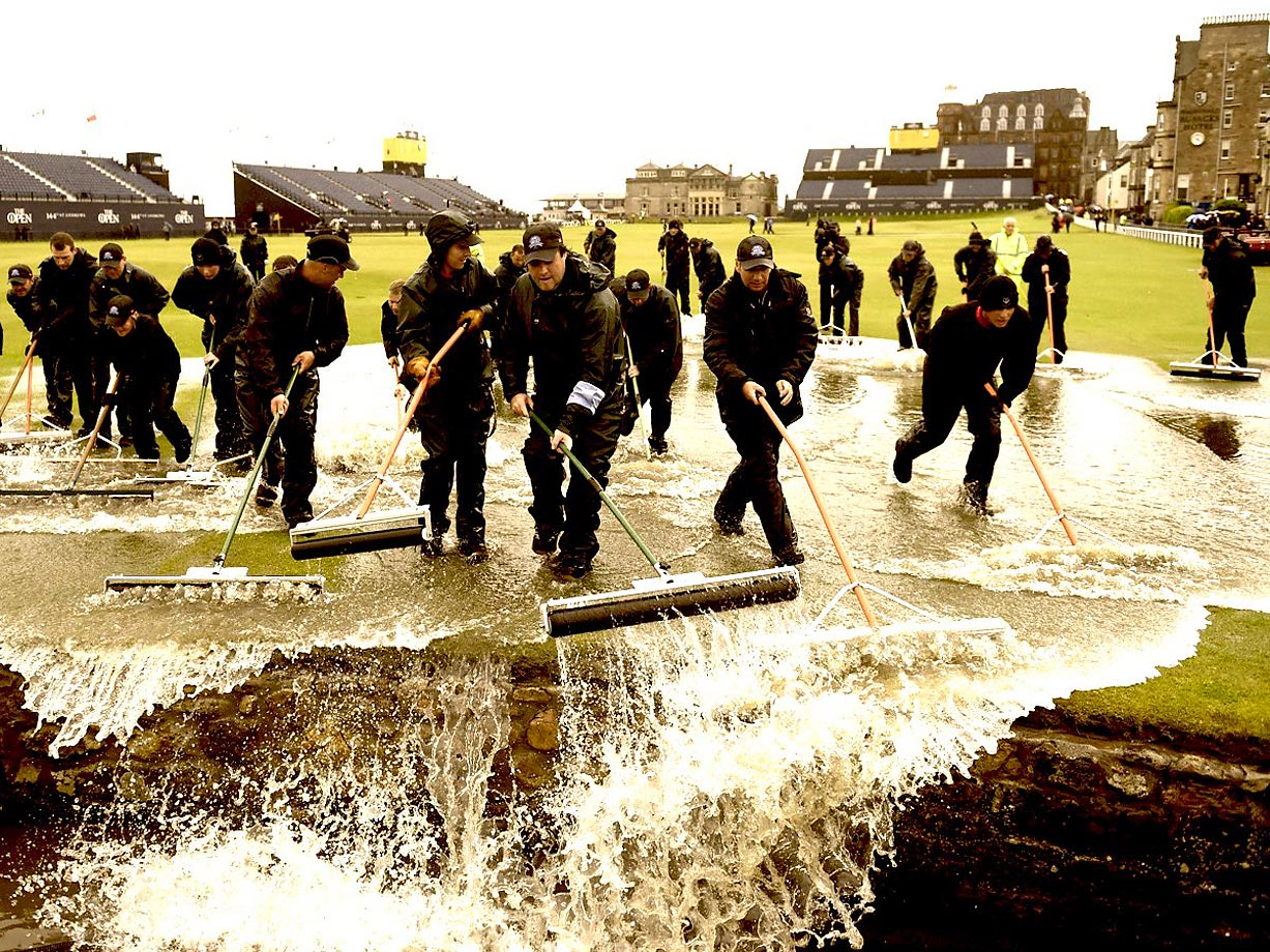 The grounds crew uses squeegees direct water into the Swilcan Burn at St. Andrews.