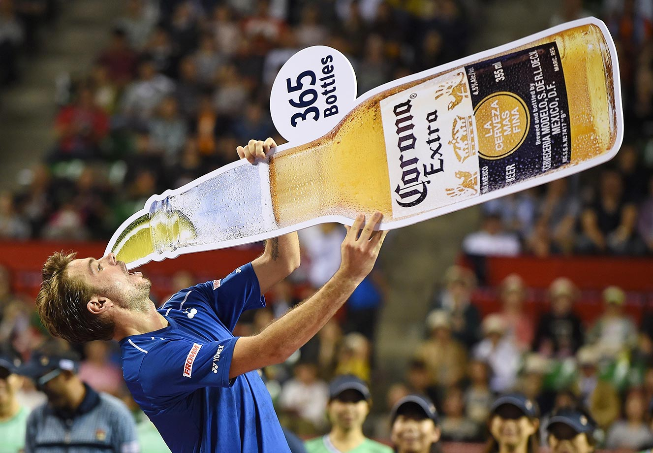 Stan Wawrinka pretends to drink a beer as he celebrates his win over Benoit Paire in the singles final match at the Japan Open.