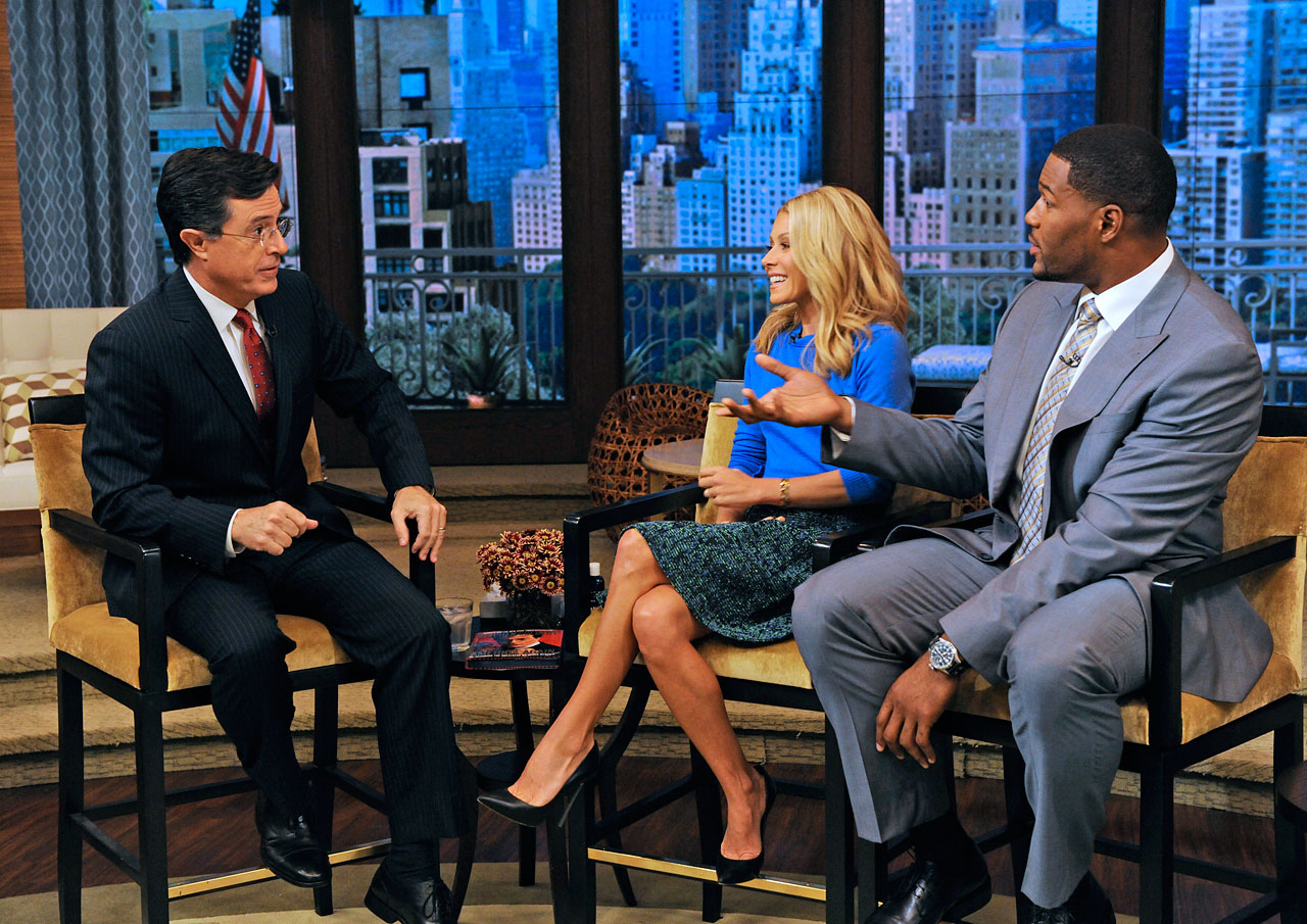 Michael Strahan asks Stephen Colbert a question on LIVE! with Kelly and Michael on Oct. 3, 2012 in New York City.