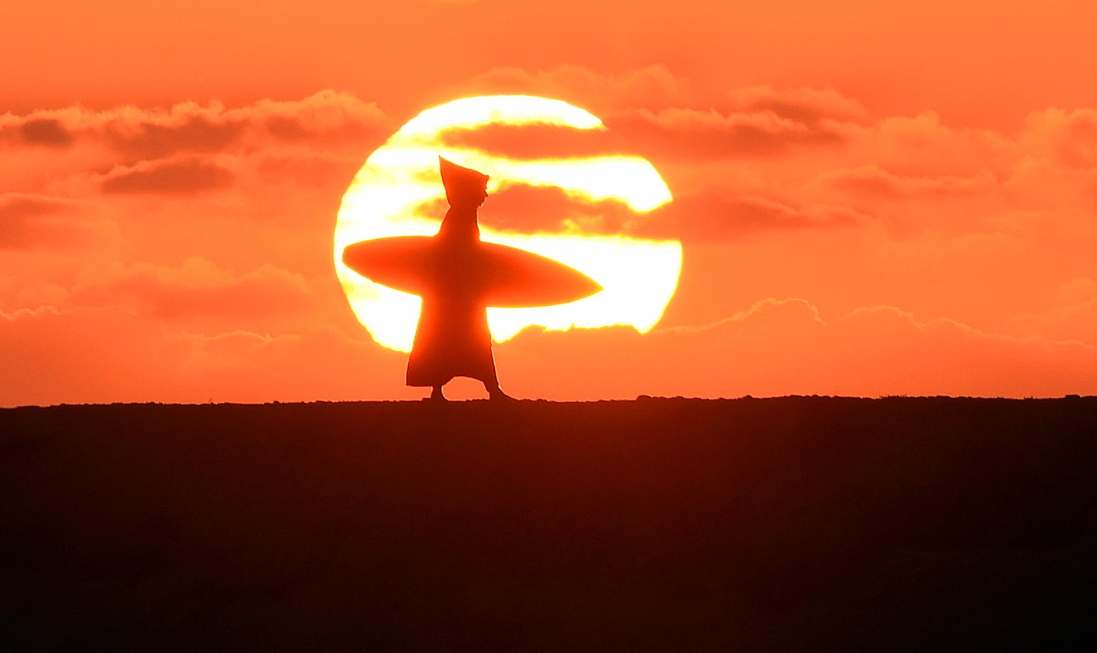 A Moroccan surfer walks along the beach as the sun sets in Oued Charrat.