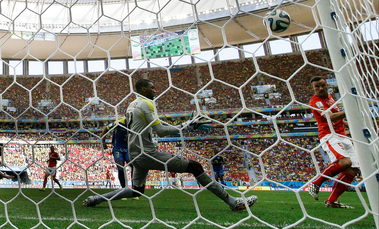 Switzerland's Haris Seferovic scores his side's winning goal past Ecuador's goalkeeper Alexander Dominguez in stoppage time during a 2-1 win on Sunday, June  15, at the Estadio Nacional in Brasilia, Brazil.It was the latest goal scored in a group stage game in World Cup history.