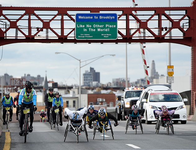 Wheelchair competitors accompanied by cyclists cross the Pulaski Bridge to enter the Queens borough of New York during the New York City Marathon.
