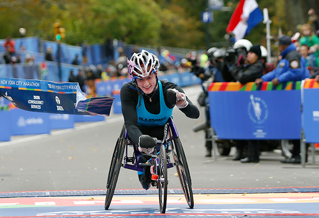 Tatyana McFadden breaks the tape after finishing first in the Women's wheelchair division of the 44th annual New York City Marathon.