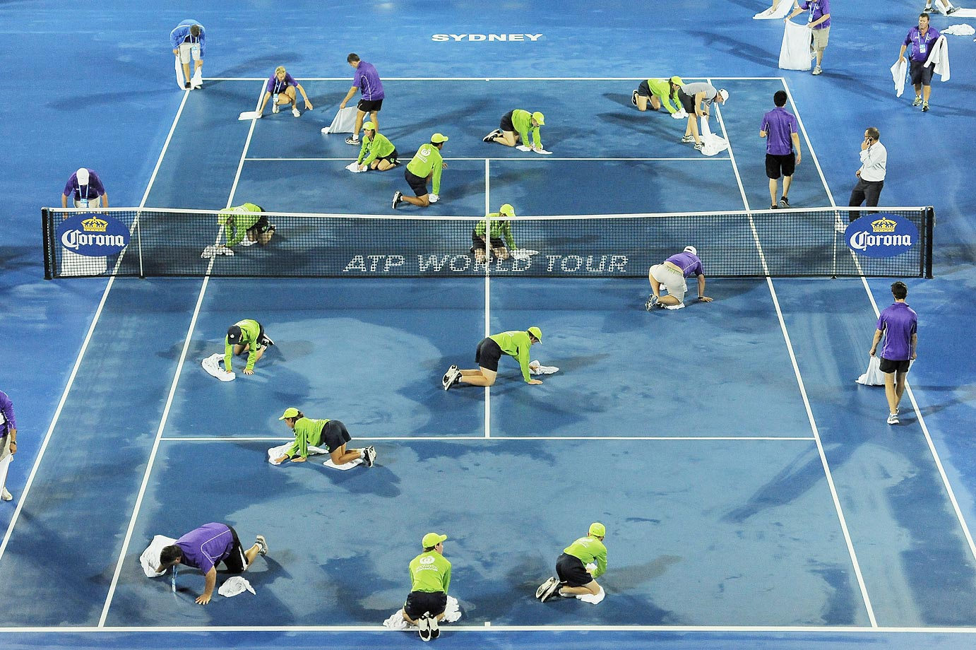 Court staff and ball kids work to dry the court ahead of the first-round match between Nick Kyrgios and Jerzy Janowicz during day three of the Sydney International.
