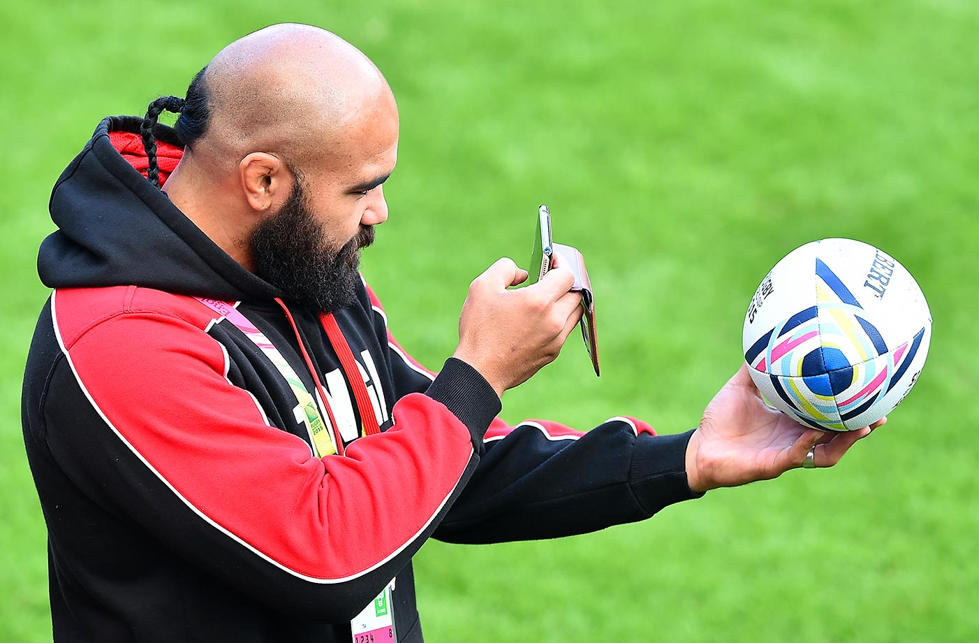 Tonga's Tevita Mailau takes a picture of the tournament's official ball at the 2015 Rugby Union World Cup pool C match.