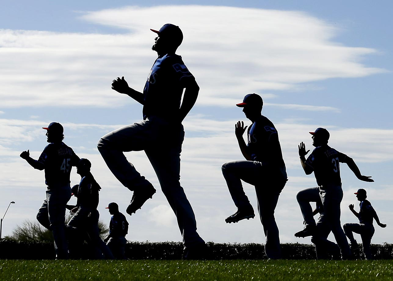 Texas Rangers players warm up during spring training baseball practice in Surprise, Ariz.