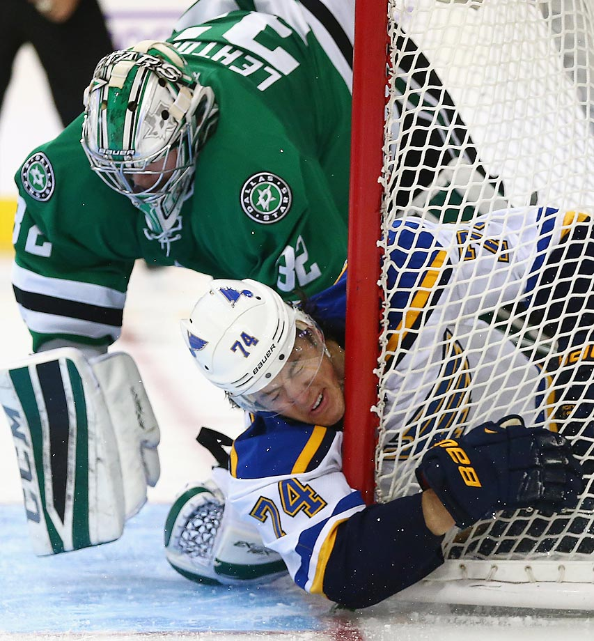 Blues winger T.J. Oshie (74) gets tangled up with Stars goaltender Kari Lehtonen.