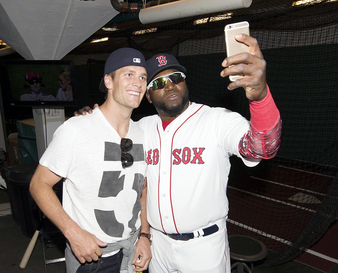 Tom Brady poses with David Ortiz after throwing out a ceremonial first pitch on Opening Day at Fenway.