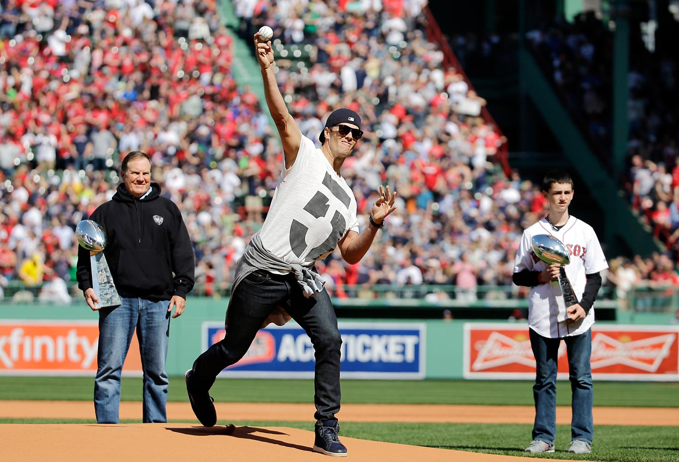 Tom Brady throws out the ceremonial first pitch, with Bill Belichick and Boston Marathon survivor Henry Richard in the background.