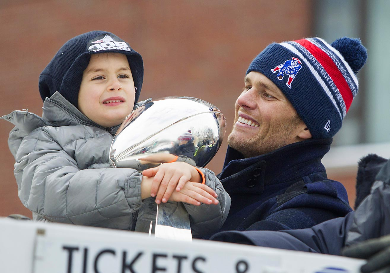 Benjamin Brady holds the Lombardi trophy next to his dad, Patriots quarterback Tom, on a duck boat during the New England Patriots victory parade.