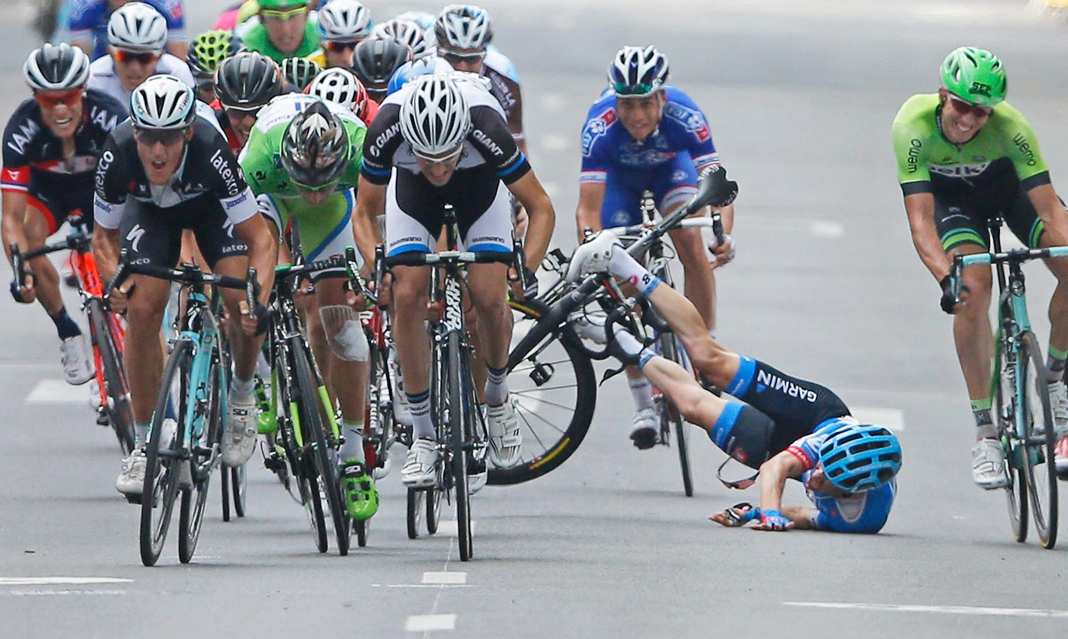 Andrew Talansky of the U.S. crashes alongside the pack as stage winner Italy's Matteo Trentin, foreground left, sprints towards the finish line during the seventh stage of the Tour de France.