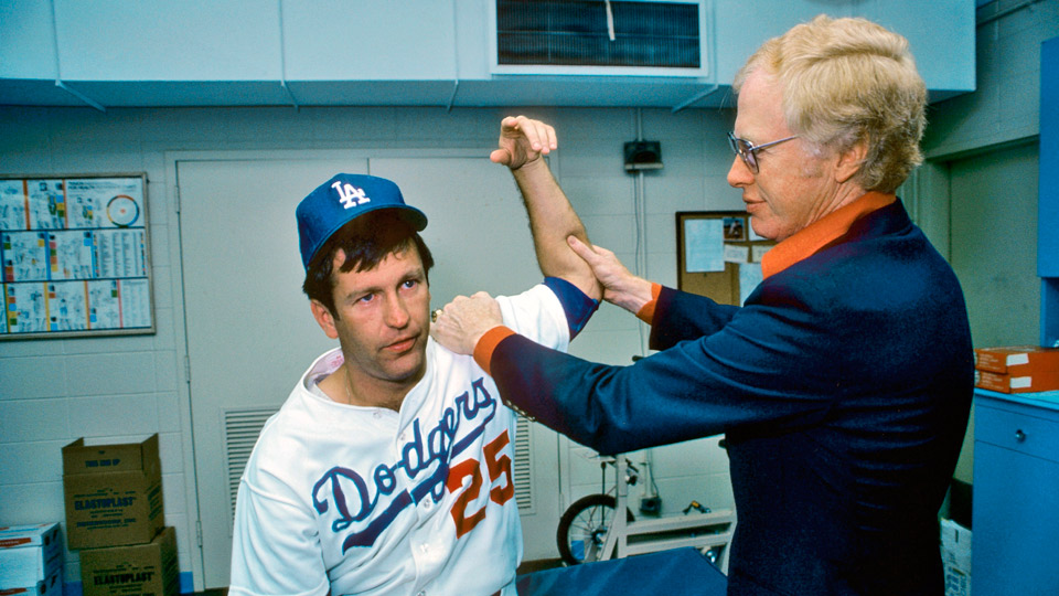 Los Angeles Dodgers orthopedist Dr. Frank Jobe examines the elbow of Tommy John in trainer's room at Dodger Stadium. Dr. Jobe previously replaced the torn ulnar collateral ligament from the elbow with a tendon from John's wrist in what would later be known as Tommy John Surgery.