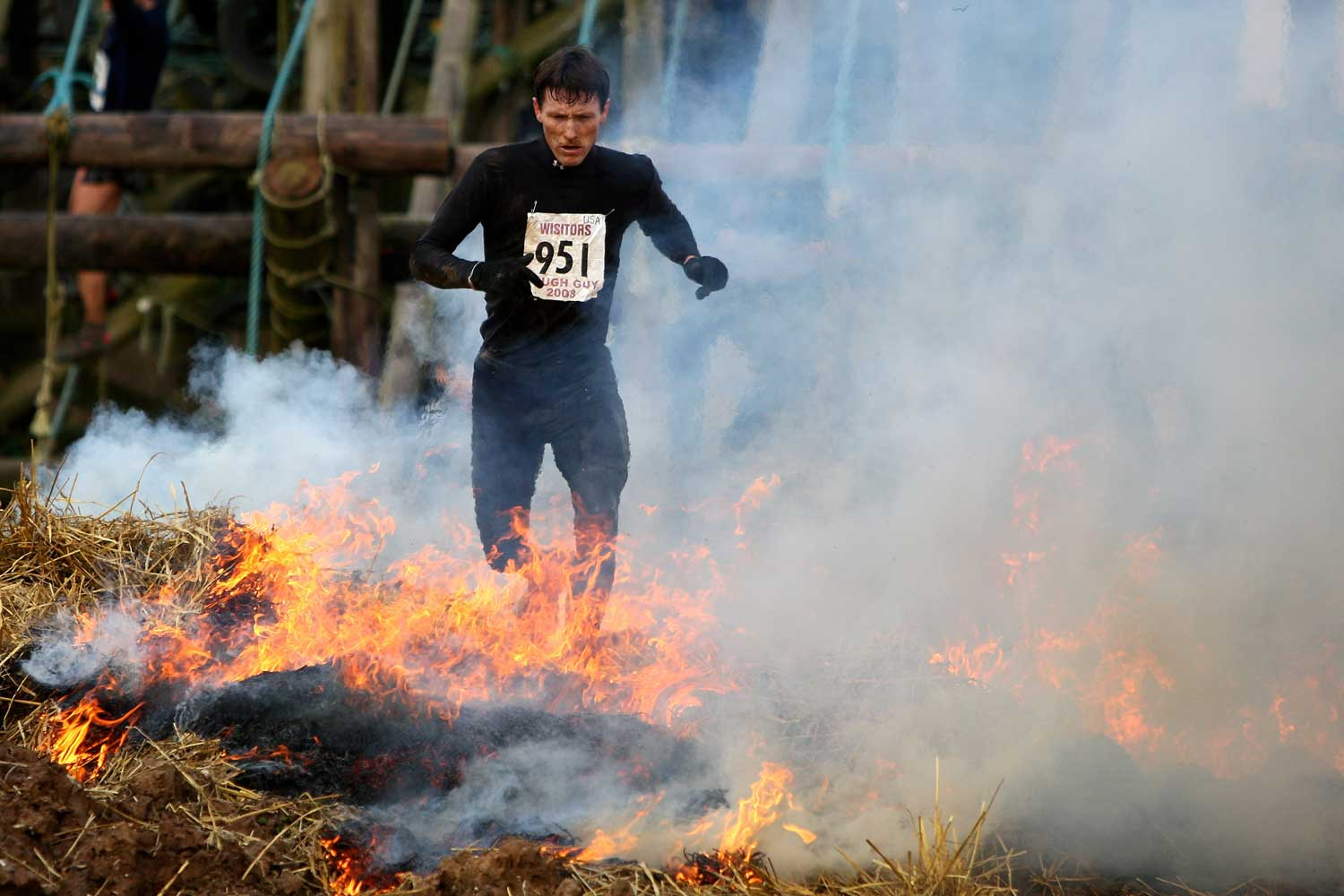 A Tough Guy Challenge competitor runs through flames during the race in Wolverhampton, England.