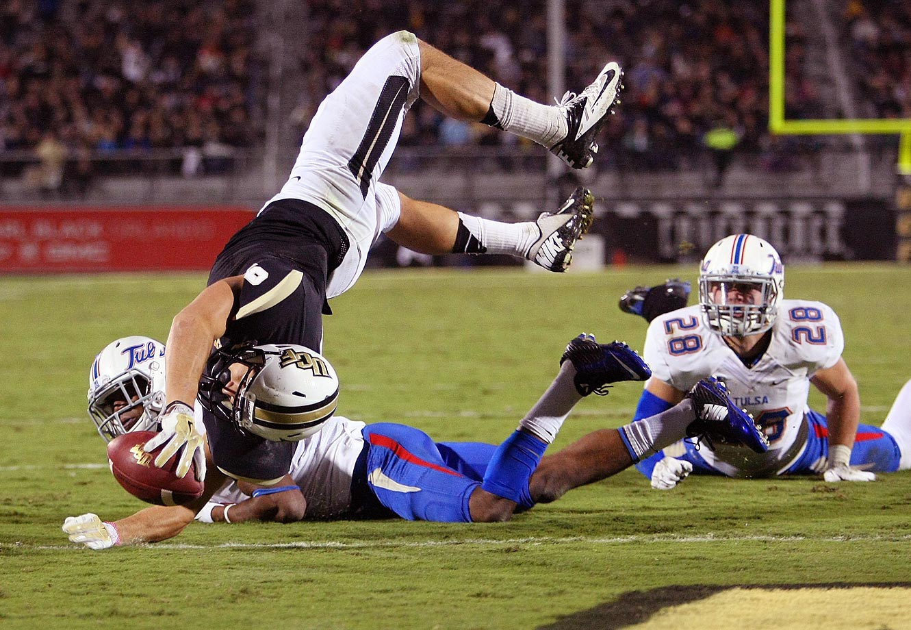 J.J. Worton of the UCF Knights leaps for a touchdown over James Flanders of the Tulsa Golden Hurricane. UCF won 31-7.